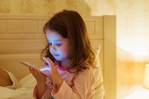 Little girl with smartphone lying in a bed, bedtime